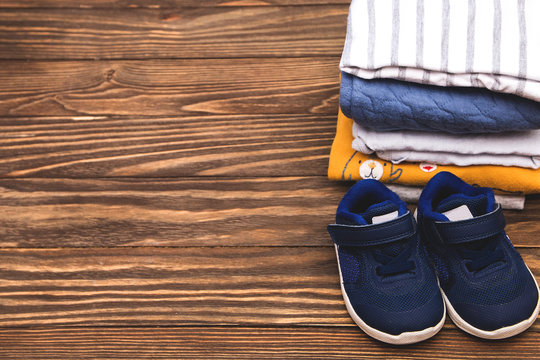 Folded bodysuits with sneakers on wooden background. Stack of children's clothes.