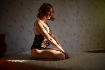 redhead girl in underwear sitting on her knees on a mattress