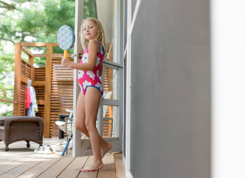 Young girl in swimsuit on porch
