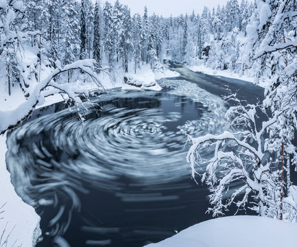 Whirlpool in black river in snowy forest