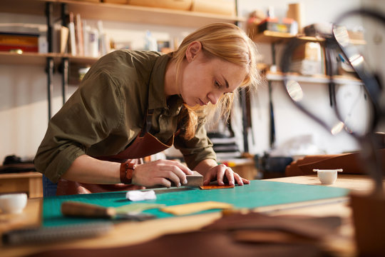 Warm toned portrait of female artisan  tracing leather patterns while working in shoemaking atelier, copy space