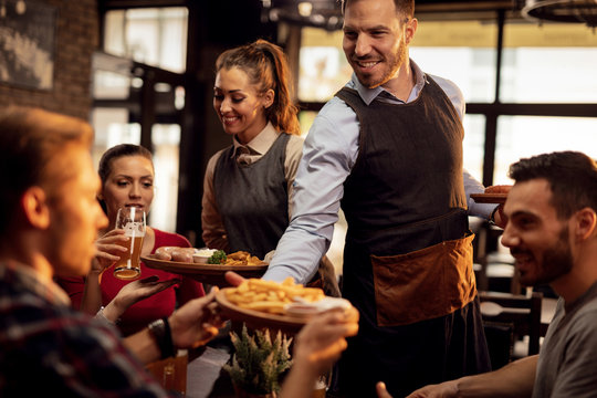 Young waiters serving lunch to group of friends in a pub.