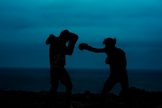Silhouettes of anonymous fighters practicing kickboxing against sea and dark sky in evening in countryside