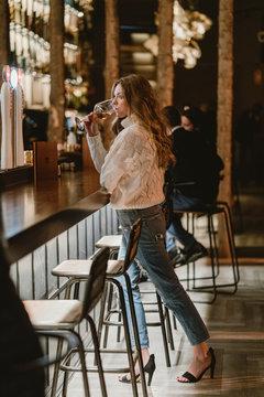 Stylish woman drinking wine in bar