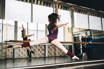 Back view of young slim ballerina jumping above ground in studio flexing legs.