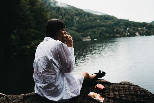 Woman eating hamburger near lake