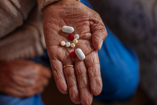 Detail of pills on the hand of an old man
