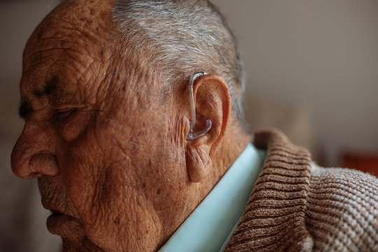Detail of a hearing aid in an old man