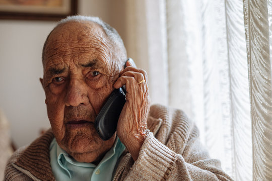 Elderly man calling from his phone inside his house