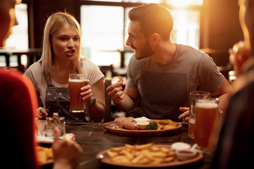 Young couple drinking beer and eating lunch with friends in a pub. Wall mural