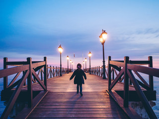 back view of anonymous girl by a beach pier at night Fotomurales