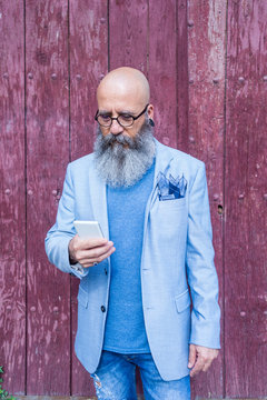 Front view of a mature trendy bearded hipster standing against a red vintage door outdoors while using a mobile phone