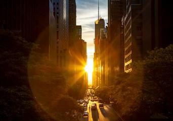 Rays of sunlight shining between the skyline buildings along 42nd Street in Midtown Manhattan, New York City