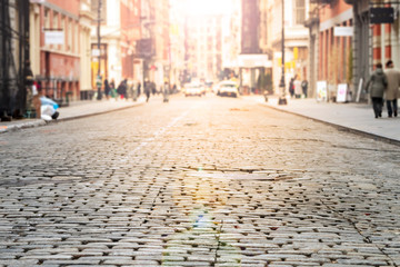 Fotomurales - New York City - Cobblestone street view in Soho with bright sunlight background
