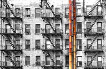 Black and white apartment building with colorful old rusted metal pipes in New York City