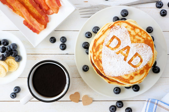 Fathers Day pancakes with heart shape and DAD letters. Fathers Day breakfast concept. Above view table scene on a white wood background.
