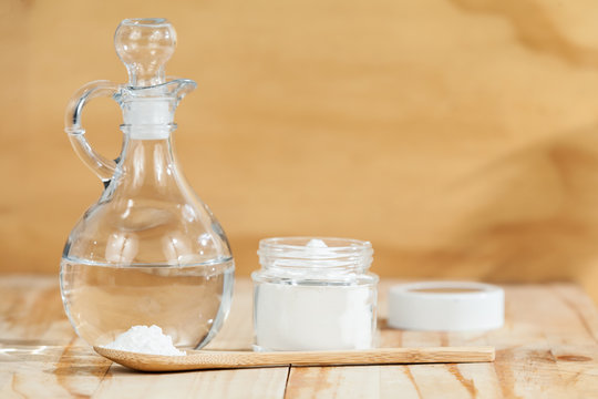 baking soda - sodium bicarbonate and vinegar, on wooden background
