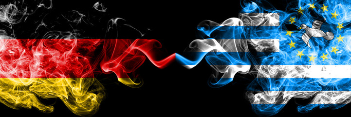 Germany vs South Cameroon smoky mystic flags placed side by side. Thick colored silky smoke flags of Deutschland and South Cameroon