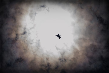 Fighter jet high in the sky against the sun