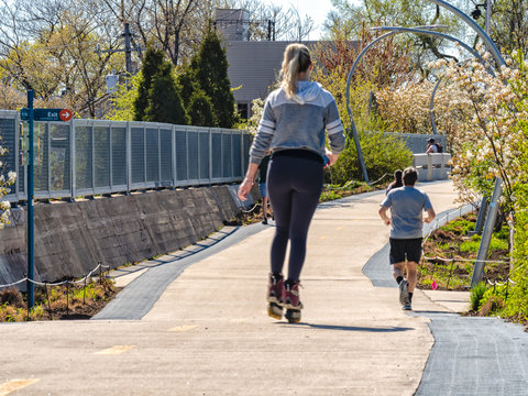 A woman is rollerblading riding skates and a man is jogging on The 606 Bloomingdale Train in Humboldt Park. Streets of Chicago, main streets in Illinois.