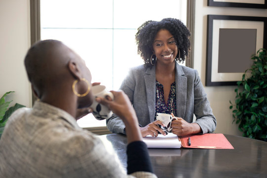 Black African American female businesswomen talking in an office.  The two women looks like a start up co workers or small business partners.