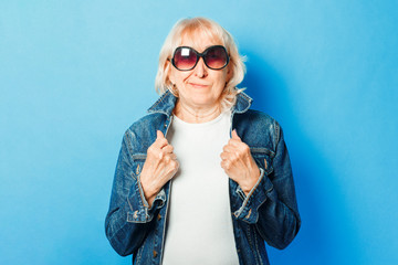 Old lady in a denim jacket and sunglasses on a blue background.