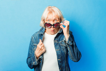 An old lady in a denim jacket, sunglasses and a surprised face on a blue background. Concept fashionable grandma, old woman.