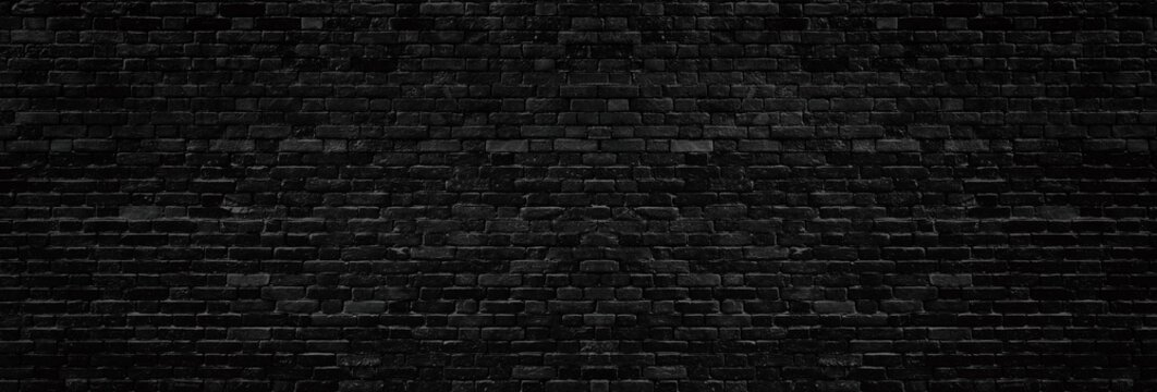 Wide old black shabby brick wall texture. Dark masonry panorama. Brickwork panoramic grunge background