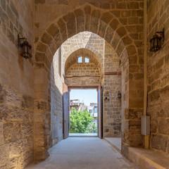 Passage at Al-Muayyad Bimaristan (hospital) historic building with stone bricks wall, stone arches, and entrance door, Darb Al Labana district, Old Cairo, Egypt