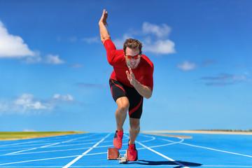 Fototapeta Runner athlete starting running at start of run track on blue running tracks at outdoor athletics and fiel stadium. Sprinter on race. Sport and fitness man sprinting. obraz