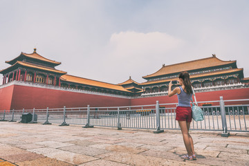 China travel lifestyle. Asian woman taking smartphone picture of Beijing tourist attraction, ancient dynasty building.