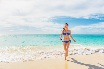 Wall Mural - Vacation summer beach bikini girl lifestyle happy woman running out of blue ocean water swimming in tropical Caribbean holiday travel destination.