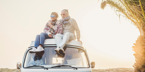 Wanderlust and travel destination happiness concept with old senior beautiful couple sitting and enjoying the outdoor freedom on the roof of vintage van vehicle together - sun backlight Fototapete