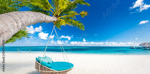 Wall mural Tropical beach background as summer landscape with beach swing or hammock and white sand and calm sea for beach banner. Perfect beach scene vacation and summer holiday concept. Boost up color process