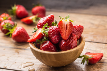 Juicy washed strawberries in wooden bowl on kitchen table