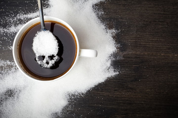 unhealthy white sugar concept. Scull spoon with sugar and cup of black coffee on wooden background Wall mural