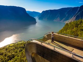 Tourist enjoying fjord view on Stegastein viewpoint Norway