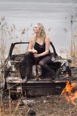 Strong rebel woman. Snatdnig on a burned car. Rebel,burned car, burning car