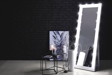 Big mirror with table near dark wall in room