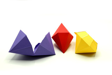 Geometric shapes cut out of colored paper and photographed from above on white background. Geometry net of Octagonal Dipyramid. 2D shape that can be folded to form a 3D shape or a solid.