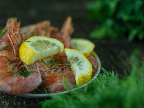 Boiled shrimps with lemons, greens and sauce on a wooden background. Side view