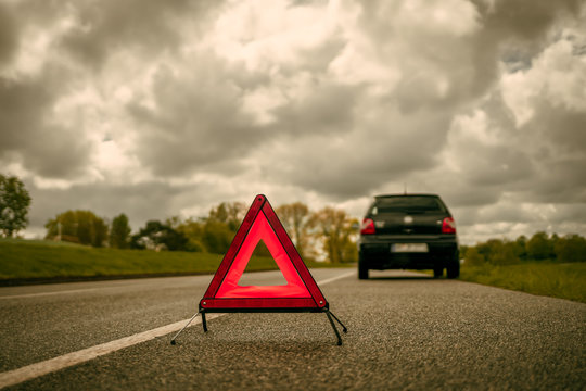 A warning triangle in front of a car with a breakdown on a side strip