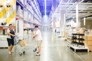 mother and son are pushing a shopping cart in warehouse for shopping