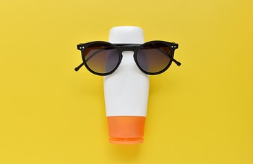 Sun protection concept, opened sunscreen lotion and sunglasses create funny face, yellow background.