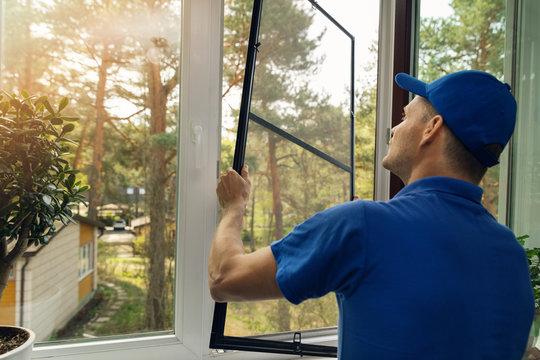 worker installing mosquito net wire screen on house window