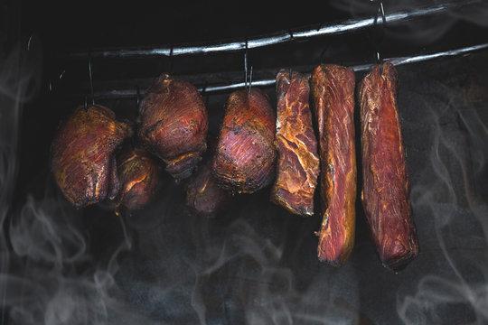 Smoked pork meat in smoker on dark background.