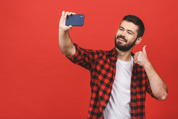 Close up portrait of a cheerful bearded man taking selfie over red background. Thumbs up.
