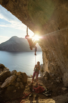 Male rock climber starting challenging route on cliff at sunset, female climber belaying him