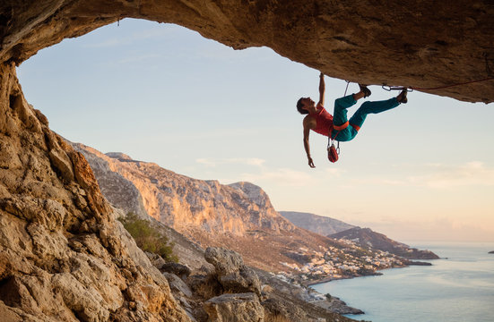 Caucasian man climbing challenging route going along ceiling in cave at sunset