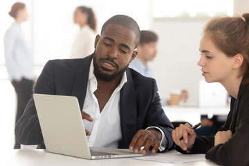 Black broker insurer consulting working with client looking at laptop